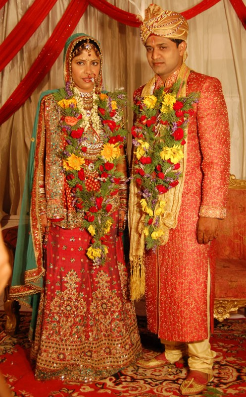 Me wearing a red lehenga with green choli and dupatta with my hubby wearing a red sherwani