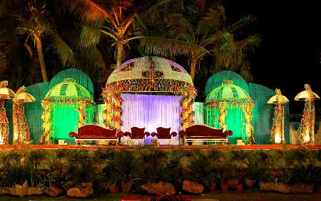 Green colored stage decoration with trees around